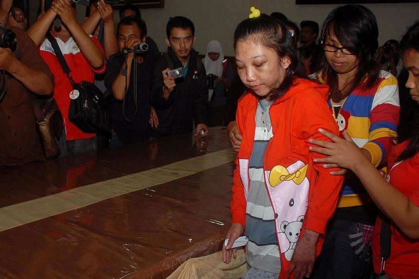 Indonesian maid Erwiana Sulistyaningsih (centre), 23, is assisted before a press conference at a hospital in Sragen district in central Java island on Feb 5, 2014.Time magazine has named Sulistyaningsihas one of the world's 100 most influ