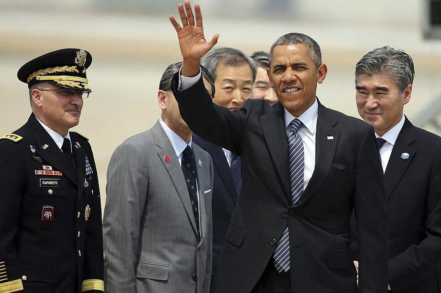 US President Barack Obama waves upon his arrival at Osan Air Base on April 25, 2014. Mr Obama arrived in Seoul on Friday to growing signs North Korea was defiantly readying another nuclear test, and with South Koreans in a state of national mourning
