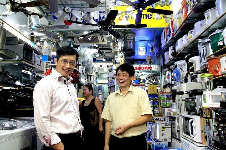 Mr Teo Ser Luck (left) with Mr Richard Teh of New City Electrical Trading. Mr Teh used to use hardcopy documents to track inventories, but is now using an electronic system.