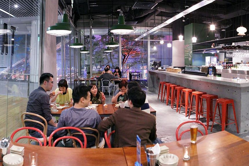 People eating at Tanuki Raw at Orchard Central which serves Japanese-inspired dishes with a focus on raw food such as oysters.-- PHOTO:TANUKI RAW