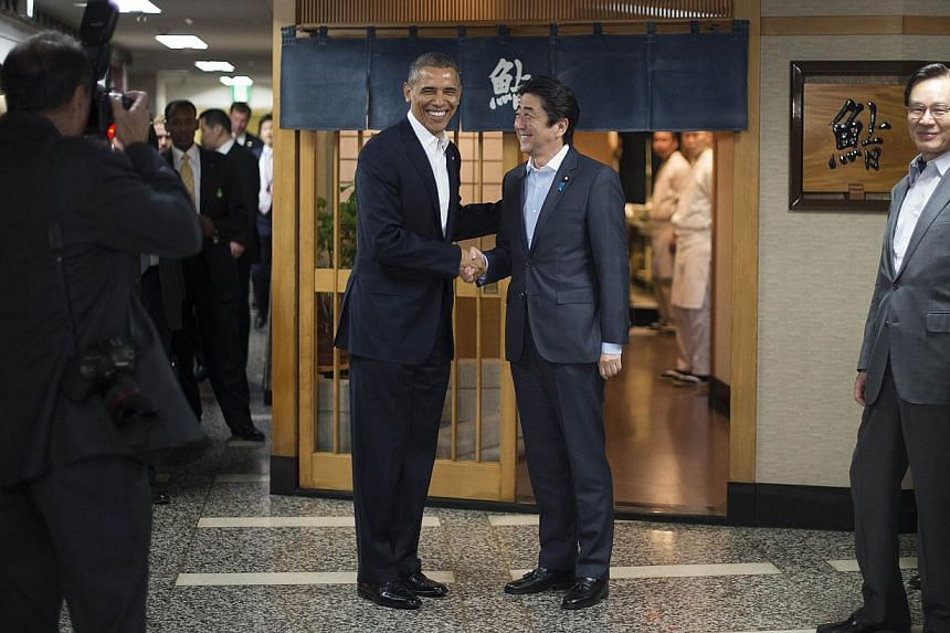 US President Obama (left) and Japanese Prime Minister Abe shake hands before a private dinner on Wednesday. The US leader's trip to Japan has been overshadowed by differences over how the two allies should deal with China. -- PHOTO: AGENCE FRANCE-P