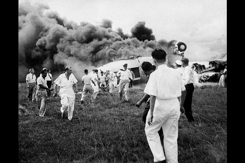 Rescuers frantically dragging an air hostess from a burning Qantas-BOAC Constellation which crashed at Kallang Airport in 1954. Thirty-two people, including all the passengers, were killed. This picture taken by the late Straits Times cameraman Sam K