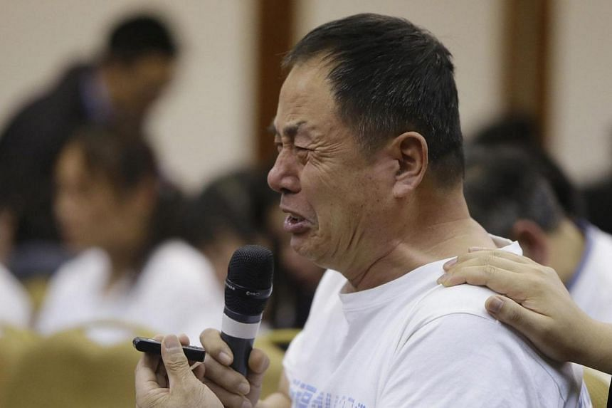 A father whose son was aboard Malaysia Airlines flight MH370, cries as he asks a question during a briefing given by Malaysian representatives at Lido Hotel in Beijing on April 21, 2014. Angry relatives of people missing on Malaysia Airlines fli