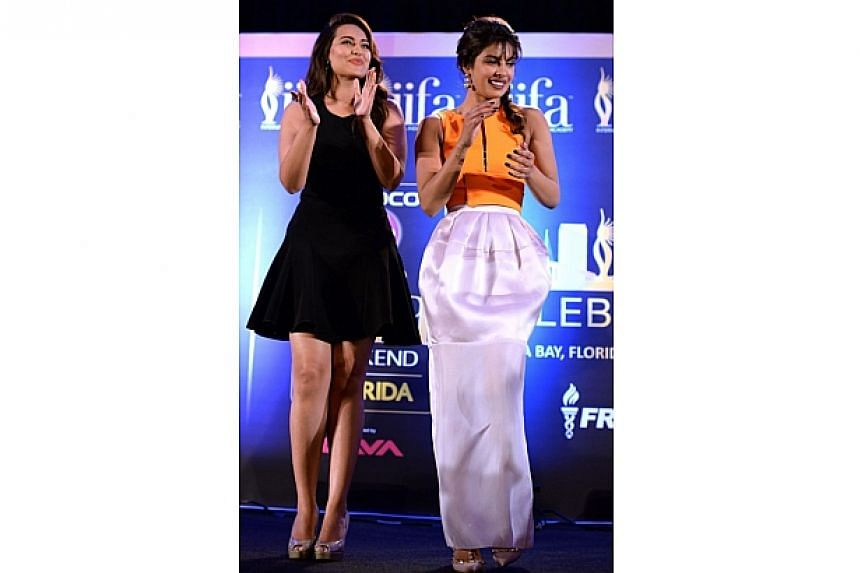 Bollywood actress Priyanka Chopra (right) and nominee for Best Performance in a Leading Role, Bollywood actress Sonakshi Sinha, on stage during a press conference at the Hilton Downtown Hotel on the second day of the 15th International Indian Film Ac
