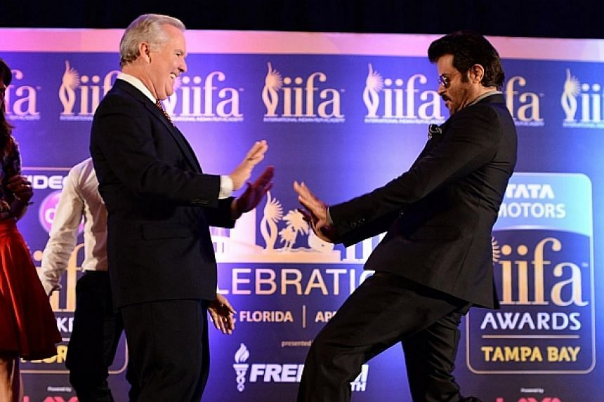 Bollywood star Anil Kapoor (right) and the mayor of Tampa Bob Buckhorn dancing to the tune of the IIFA anthem Do Da Tampa on stage during a press conference at the Hilton Downtown Hotel on the second day of the 15th International Indian Film Academy
