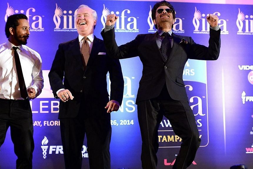 Bollywood star Anil Kapoor (right) and an unidentified background dancer engage the mayor of Tampa Bob Buckhorn (centre) into a dance to the tune of the IIFA anthem Do Da Tampa on stage during a press conference at the Hilton Downtown Hotel on the se