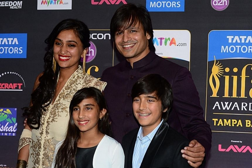 Bollywood actor Vivek Oberoi posing with his family on the green carpet at the Tampa Convention Center ahead of IIFA Rocks on the second day of the 15th International Indian Film Academy (IIFA) Awards in Tampa, Florida, on April 24, 2014. -- PHOTO: A