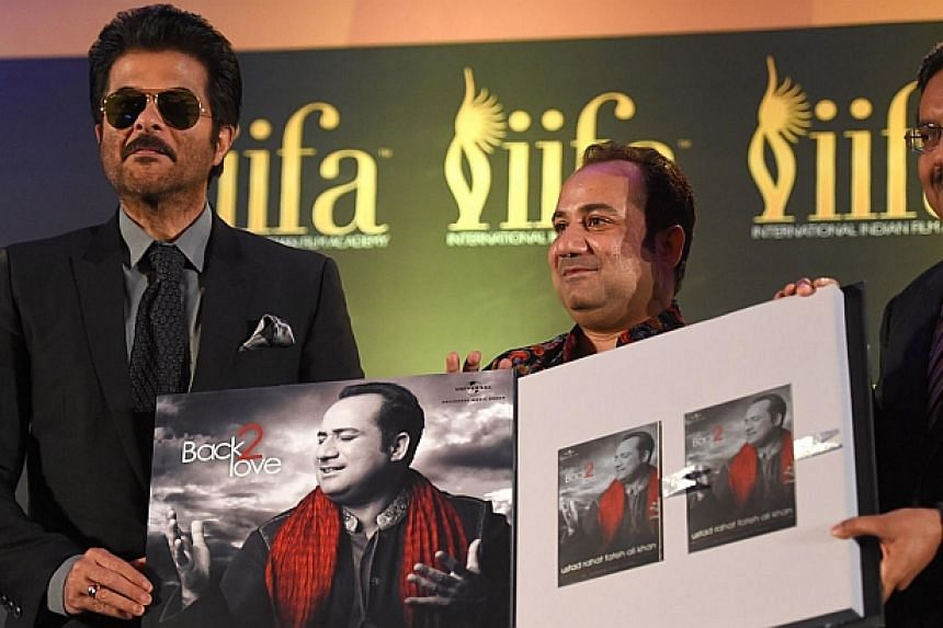 Bollywood singer Rahat Fateh Ali Khan (centre), with actor Anil Kapoor (left), presenting his latest release during a press conference at the Hilton Downtown Hotel on the second day of the 15th International Indian Film Academy (IIFA) Awards in Tampa