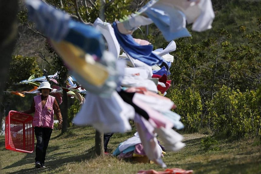 A volunteer hangs clothes of family members of a missing passenger on board the capsized South Korean ferry Sewol, up to dry at a makeshift accommodation at a gymnasium in the port city of Jindo on April 24, 2014.A small army of volunteers, off
