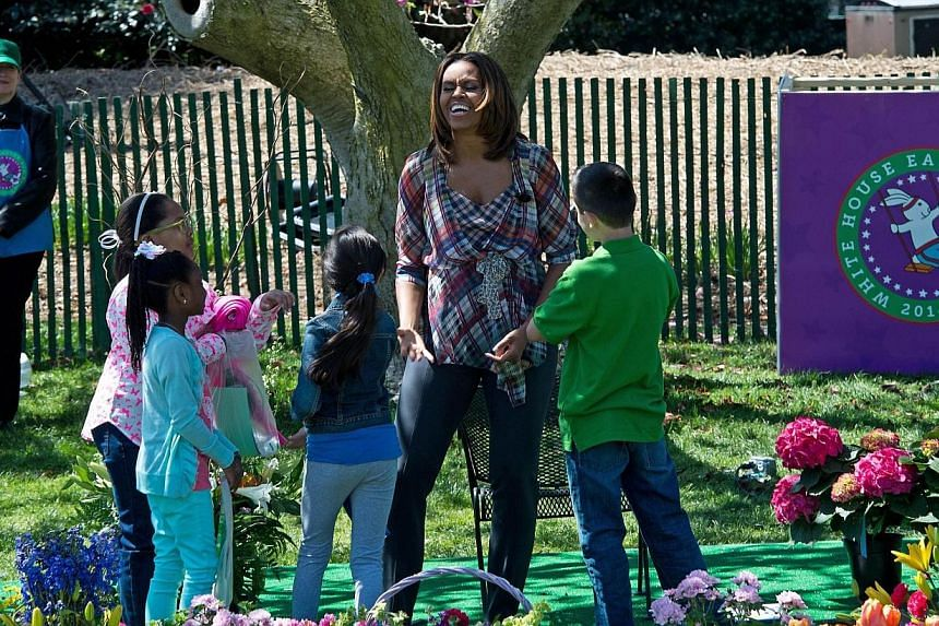 """US First Lady Michelle Obama greets children after reading """"My Garden"""" by Kevin Henkes during the annual Easter Egg Roll at the White House in Washington on April 21, 2014. -- FILE PHOTO: AFP"""