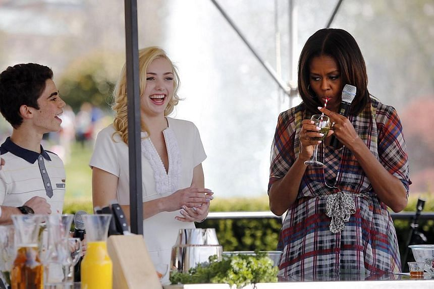 U.S. first lady Michelle Obama (right) tastes a kale smoothie during a healthy cooking demonstration with chef Marc Murphy (left-right) and young actors Cameron Boyce and Peyton List during the annual Easter Egg Roll on the South Lawn of the White Ho