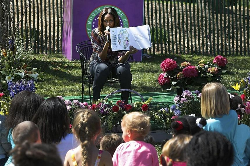 """U.S. first lady Michelle Obama reads to children from the book """"My Garden"""" during the annual Easter Egg Roll on the South Lawn of the White House in Washington on April 21, 2014. -- FILE PHOTO: REUTERS"""
