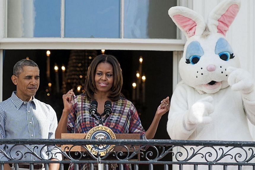 US First Lady Michelle Obama speaks alongside President Barack Obama and the Easter Bunny during the annual White House Easter Egg Roll on the South Lawn of the White House in Washington, DC on April 21, 2014. -- FILE PHOTO: AFP
