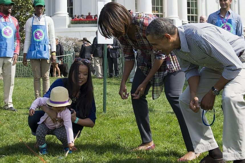 US President Barack Obama and First Lady Michelle Obama react to a child rolling an Easter egg during the annual White House Easter Egg Roll on the South Lawn of the White House in Washington, DC on April 21, 2014. -- FILE PHOTO: AFP