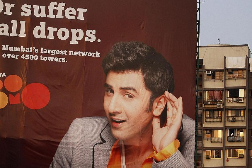 A billboard advertisement for Tata DoCoMo, the joint venture between NTT DoCoMo and Tata Teleservices, stands in front of residential buildings in Mumbai, India on Tuesday, Nov 15, 2011. -- FILE PHOTO: BLOOMBERG