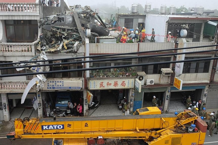 Rescure workers lift a damaged US-made AH-64E Apache attack helicopter (top left) from a roof in Taoyuan, northern Taiwan on April 25, 2014. -- PHOTO: AFP