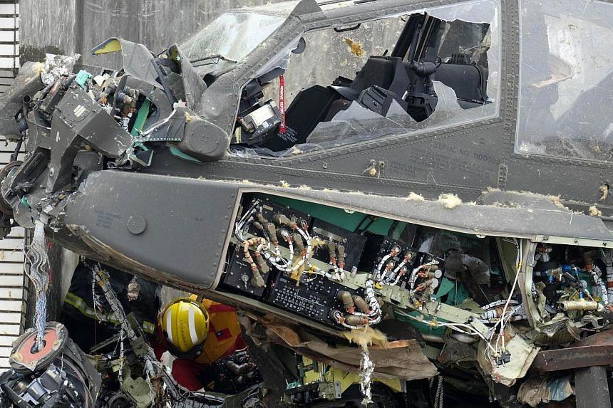 A rescue worker checks a damaged US-made AH-64E Apache attack helicopter which crashed on a roof in Taoyuan, northern Taiwan on April 25, 2014. -- PHOTO: AFP