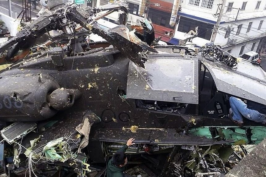 An AH-64E Apache attack helicopter purchased from the US is seen crashed on top of an apartment in Taoyuan County, northern Taiwan, April 25, 2014. The incident occurred at around 10am local time (0200 GMT) on Friday in the middle of Taiwan Army mili