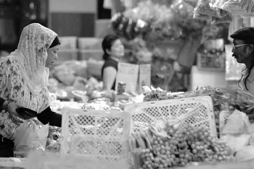 A woman checking out the vegetables at the dry goods section of the market.-- PHOTOS: SINGAPORE PRESS HOLDINGS AND NATIONAL HERITAGE BOARD