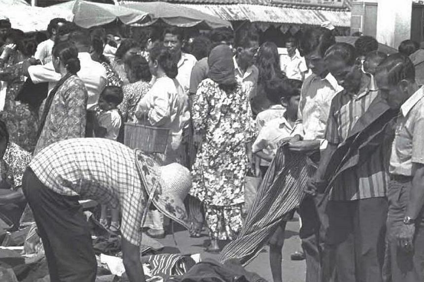 Hari Raya shoppers at the roadside stalls along Geylang Serai flats in the 1970s. -- PHOTOS: SINGAPORE PRESS HOLDINGS AND NATIONAL HERITAGE BOARD
