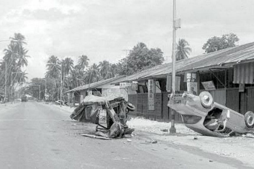 Two overturned cars at Paya Lebar Road, near the Geylang Fire Station, in 1964. -- PHOTOS: SINGAPORE PRESS HOLDINGS AND NATIONAL HERITAGE BOARD