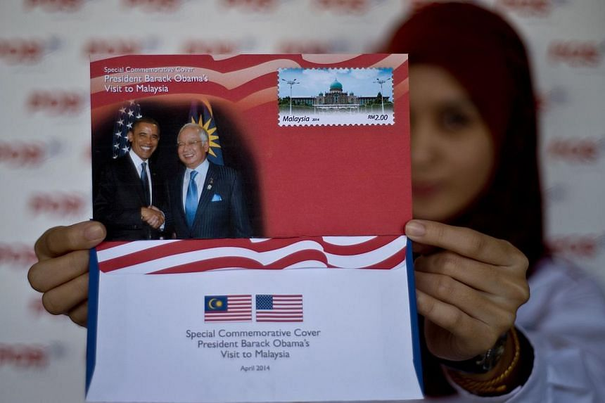 A Pos Malaysia Postal services employee poses with the special commemorative cover to mark US President Barack Obama's visit to Malaysia, in Kuala Lumpur, on April 25, 2014.Mr Obama will meet representatives of a range of civil-society groups -