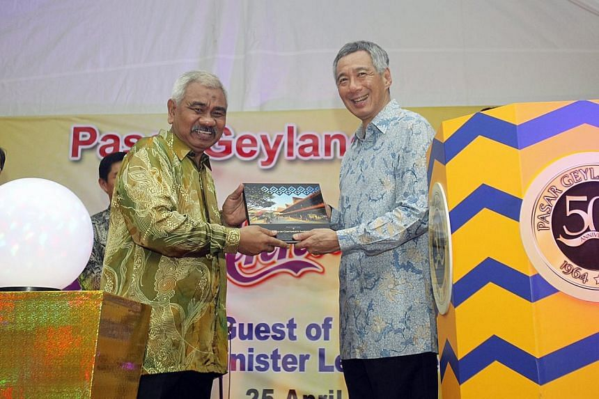 Organising chairman of Pasar Geylang Serai Merchants' Association Rahmat Sawie presenting PM Lee Hsien Loong with the commemorative book during Pasar Geylang Serai's 50th Anniversary Celebrations on April 25, 2014. -- ST PHOTO: KEVIN LIM