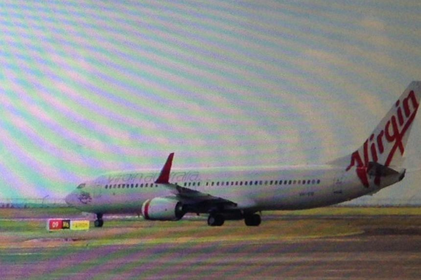This photo taken through the window of a plane shows a Virgin Australia plane at the centre of a hijacking scare sitting on the tarmac at Bali airport in Denpasar, on April 25, 2014. A drunk passenger sparked a hijacking alert on a Virgin Australia f