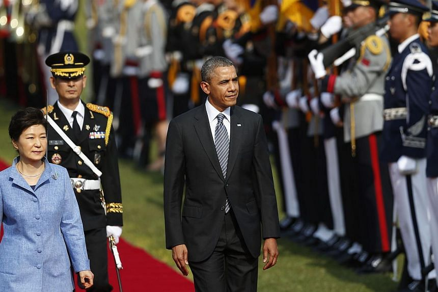 US President Barack Obama (centre) and South Korean President Park Geun Hye (left) inspect an honour guard during a welcoming ceremony at the presidential Blue House in Seoul on April 25, 2014. -- PHOTO: REUTERS