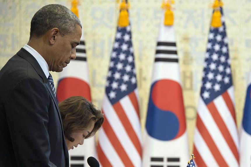 US President Barack Obama (left) stands during a moment of silence for the Sewol ferry victims during a bilateral meeting with the South Korean President at the Blue House in Seoul on April 25, 2014. -- PHOTO: AFP