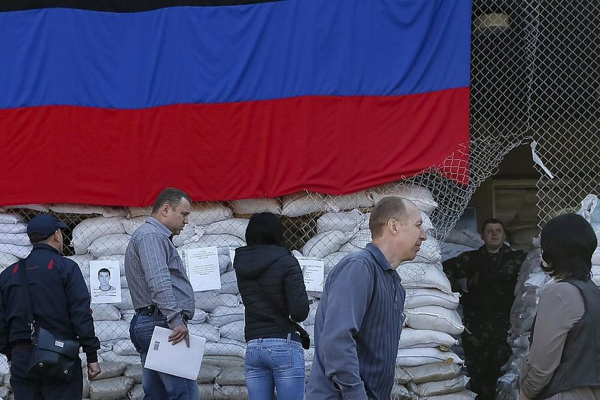 A pro-Russian armed man stands guard as local residents wait near the mayor's office in Slaviansk on April 25, 2014. The Group of Seven countries have agreed that they will impose new sanctions on Russia over the crisis in Ukraine, a statement said t