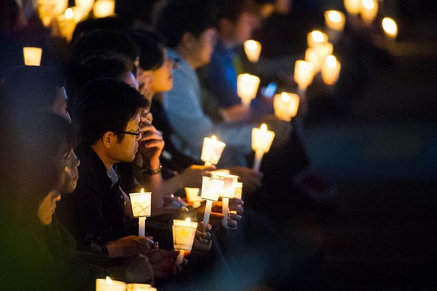 People hold candles at a vigil for students among the missing passengers of a South Korean capsized ferry, in central Ansan on April 25, 2014. -- PHOTO: AFP