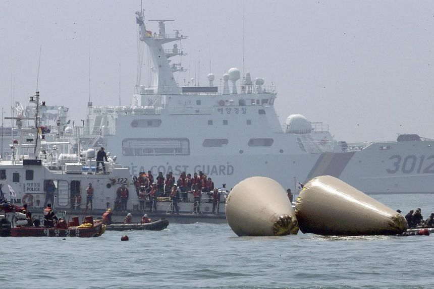 Family members (Center) of missing passengers onboard the sunken passenger ship Sewol look at South Korean rescue workers operating near floats where Sewol sank, during a rescue operation in Jindo April 24, 2014. All 15 crew members involved in
