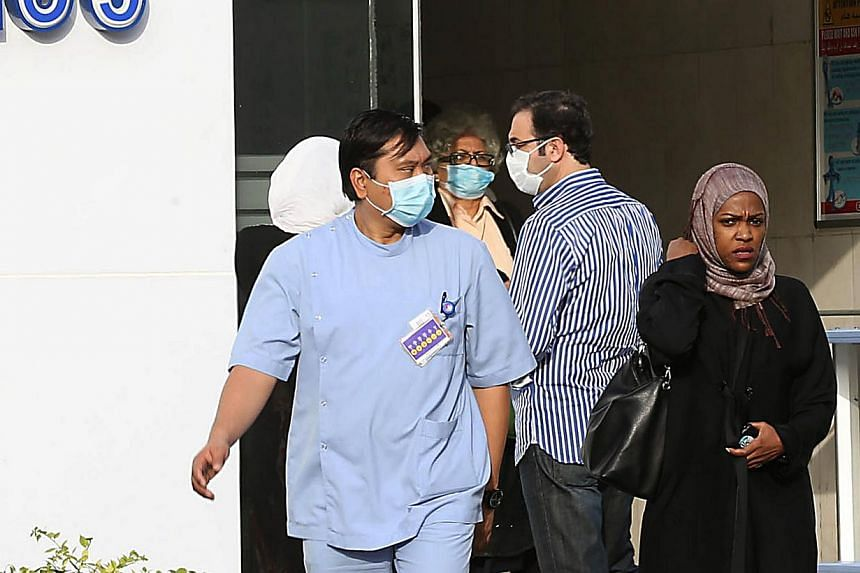 Medical workers and foreigners wear mouth and nose masks as they leave a local hospital's emergency department, on April 22, 2014 in the Red Sea coastal city of Jeddah. -- FILE PHOTO: AFP