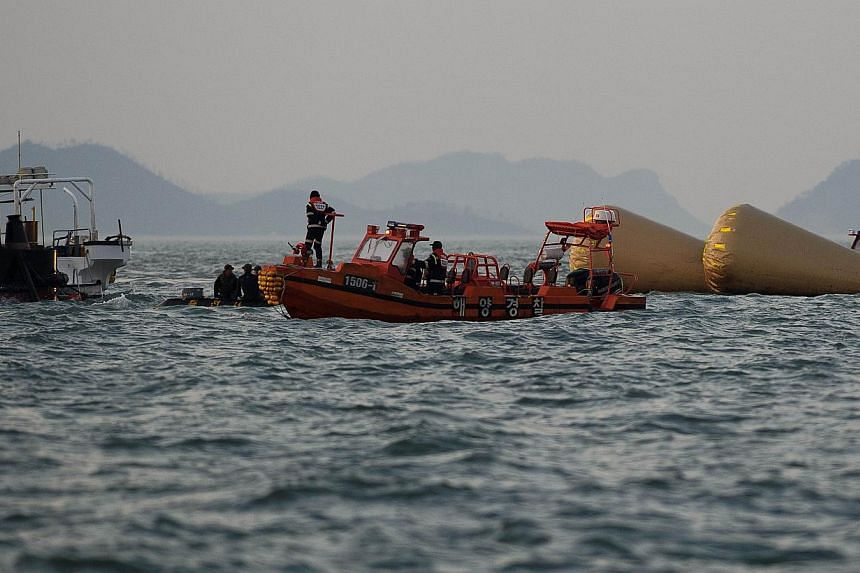 Coatguard boats and search and rescue teams take part in recovery operations at the site of the 'Sewol' ferry, off the coast of the South Korean island of Jindo on April 24, 2014. -- FILE PHOTO: AFP