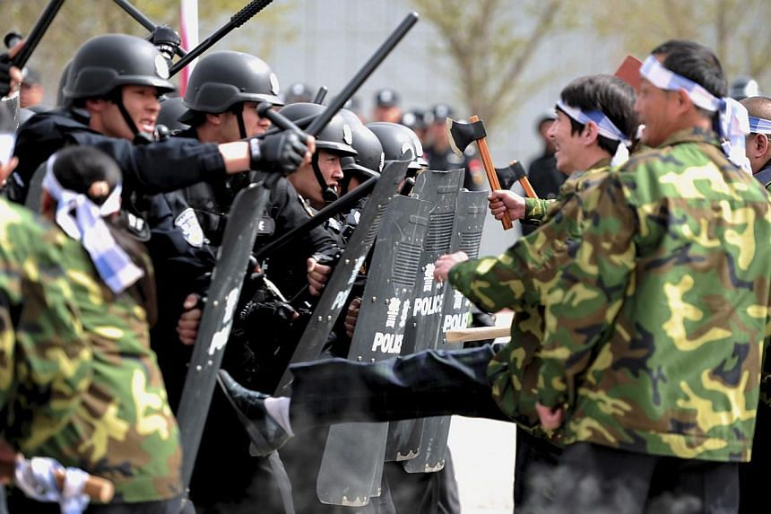 Participants playing the role of attackers confront riot policemen during a security drill in Urumqi, Xinjiang Uighur Region April 26, 2014. -- PHOTO: REUTERS