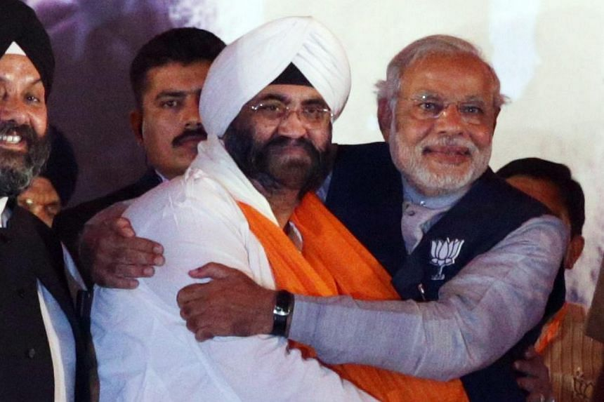 Bharatiya Janata Party (BJP) Prime Ministerial candidate Narendra Modi (right) hugging Indian Prime Minister Manmohan Singh's brother Daljeet Singh Kohli after Mr Kohli joined BJP, during an election campaign rally in Amritsar, India, on April 25, 20