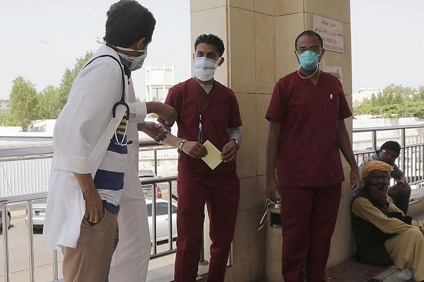 Saudi hospital employees wear mouth and nose masks as they stand outside the a local hospital's emergency department, on April 22, 2014 in the Red Sea coastal city of Jeddah. -- PHOTO: AFP