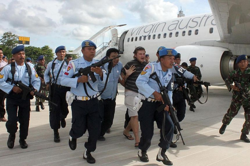 A handout released by Indonesian Air Force shows Matt Christophers Lockley (centre, back) of Australia being arrested by Indonesian Air Force soldiers after landing on the Virgin Australia 737-800 plane at Ngurah Rai airport in Denpasar on the resort