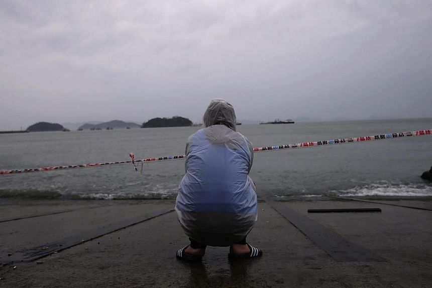 A family member of a missing passenger onboard the capsized Sewol ferry looks to the sea as he waits for the news from the search and rescue team at a port in Jindo on April 27, 2014.South Korean prosecutors raided the offices of state sea traf