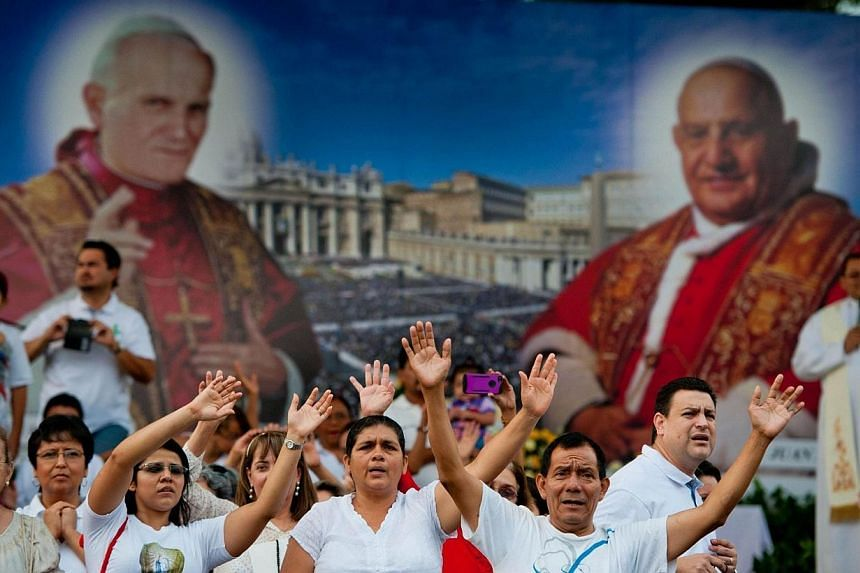Salvadorean Catholic faithfuls participate in a ceremony in San Salvador, El Salvador on April 26, 2014, on the eve of the canonisation of the late Pope John Paul II and Pope John XXIII. Pope Francis proclaimed two of his predecessors, Popes Joh