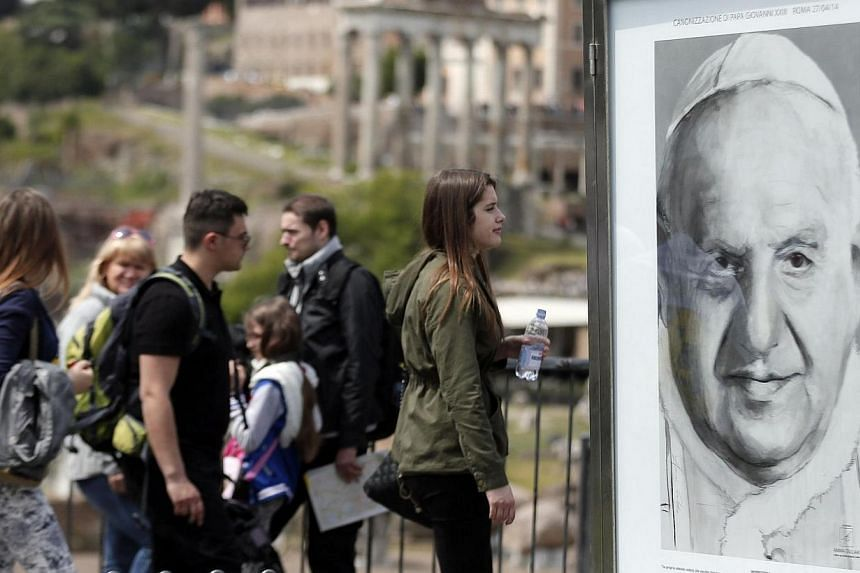 People walk past a picture featuring Pope John XXIII downtown in Rome on April 26, 2014. -- PHOTO: REUTERS