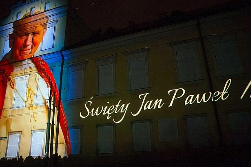 An image of Pope John Paul II is projectedduring a multimedia showin Krakow on April 26, 2014, the night before his canonisation at the Vatican. -- PHOTO: REUTERS