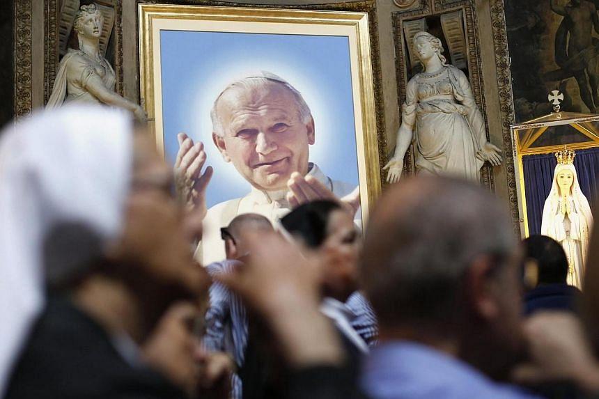A nun prays near a portrait of Pope John Paul II in a Rome church on April 26, 2014. -- PHOTO: REUTERS
