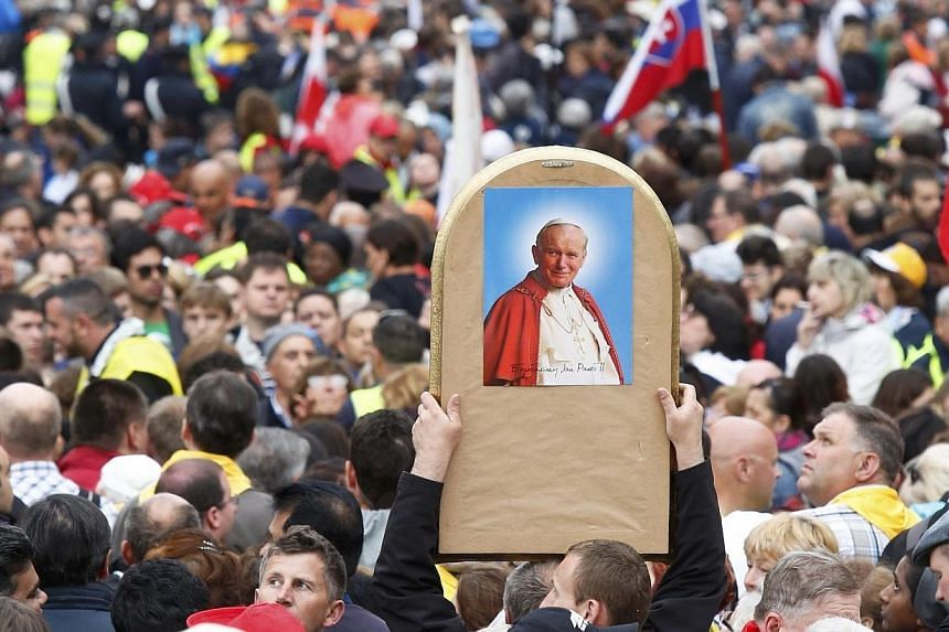 A Catholic faithful raises an image of Pope John Paul II through the crowds while waiting to attend the canonisation ceremony of Popes John XXIII and John Paul II in St. Peter's Square at the Vatican on April 27, 2014. -- PHOTO: REUTERS