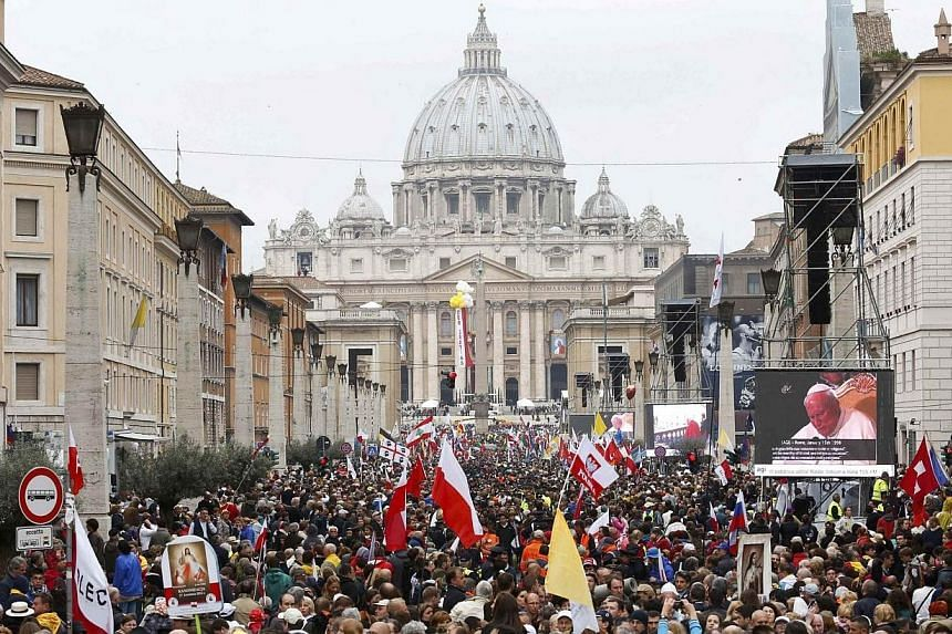 Catholic faithful gather along Via Della Conciliazione in front of St. Peter's Square to attend the canonisation ceremony of Popes John XXIII and John Paul II at the Vatican in Rome on April 27, 2014. -- PHOTO: REUTERS