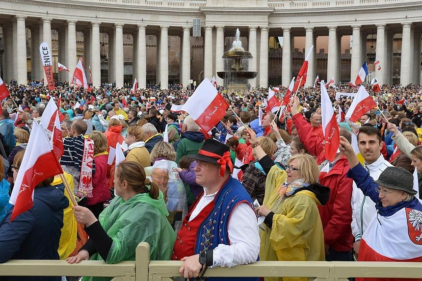 Pilgirms attend the canonisation mass of Popes John XXIII and John Paul II on St Peter's at the Vatican on April 27, 2014.Pope Francis began an historic ceremony on St Peter's Square on Sunday, April 27, 2014,to confer sainthood on two of