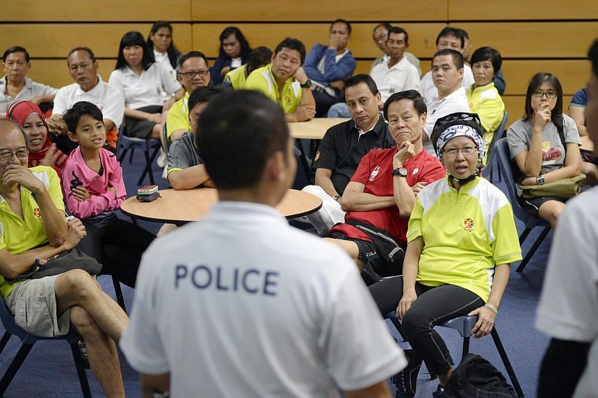 Volunteers who are taking up roles as cycling wardens in Tampines listening to a crime and road safety briefing by Staff Sergeant Firdaus Mohamad (foreground) from Changi Neighbourhood Police Centre.
