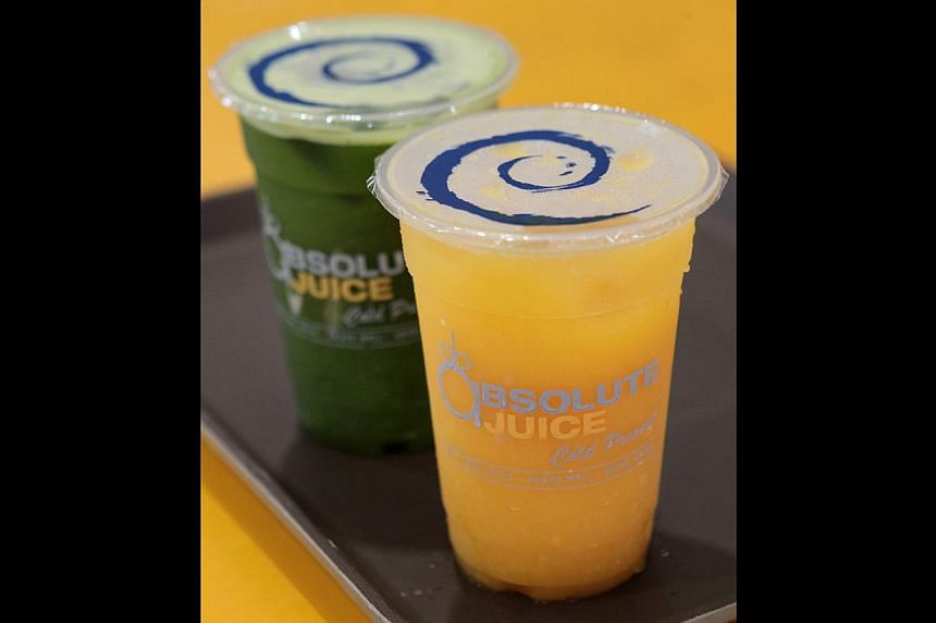 Opt for orange juice (front) or a blend such as Absolute Green (back), which consists of apple, kale, spinach, (From foreground) Freshly made celery, cucumber, ginger and lemon. -- ST PHOTO: NEO XIAOBIN