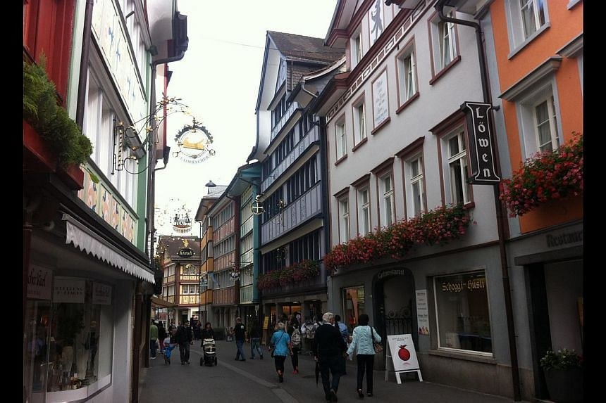 The town of Appenzell (above) has picturesque buildings dating back to the 16th century, decorated with flower-dressedwindows. Cowbells line a store window in the town. -- PHOTO: YIP WAI YEE